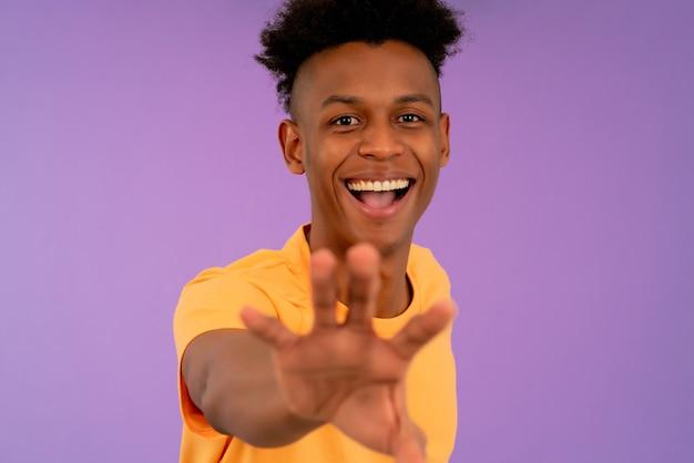 孤立した背景に立っている間、笑顔で彼の手で何かをキャッチしようとしている若いアフロ男の肖像画。