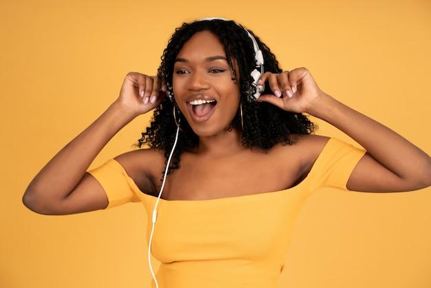 孤立した黄色の背景に立ってヘッドフォンで音楽を聴いて楽しんでいる若いアフロ女性の肖像画。