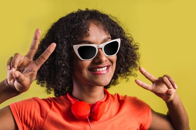 両手でvサインを作る若いアフロ女性の肖像画。