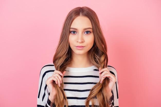 ピンクの背景のスタジオでストライプのセーターを着た若くて魅力的な10代の長髪の女性のスタイリッシュなモデルの肖像画。健康で強くて太い髪の概念