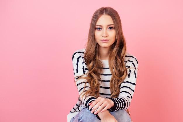 ピンクの背景のスタジオでストライプのセーターでポーズをとって若くて魅力的な10代の長髪の女性のスタイリッシュなモデルの肖像画