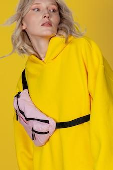 黄色のスポーツウェアで若くて魅力的な若いブロンドの女性の肖像画