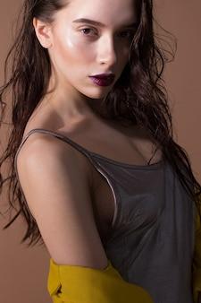 ベージュでポーズをとる若くて美しい女性の肖像画。