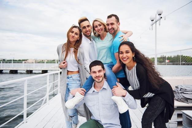 桟橋で休んでいる若い、幸せな人々の肖像画。湖でのゲームを楽しんでいる友人。ポジティブな感情。