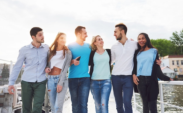 Портрет молодых и счастливых людей на отдыхе на пристани. друзья наслаждаются игрой на озере. позитивные эмоции.