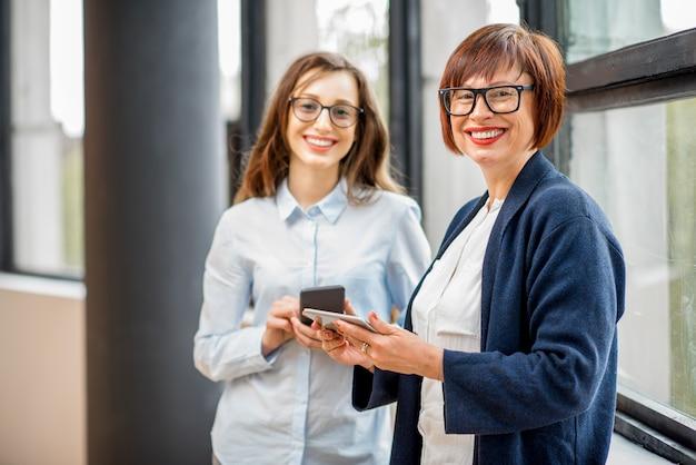 Портрет молодых и пожилых женщин-предпринимателей, стоящих у окна в офисе