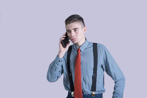 Портрет молодого и стильного мальчика в костюме разговаривает по телефону