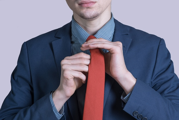 ネクタイを結ぶスーツを着た若くてスタイリッシュな男の肖像画