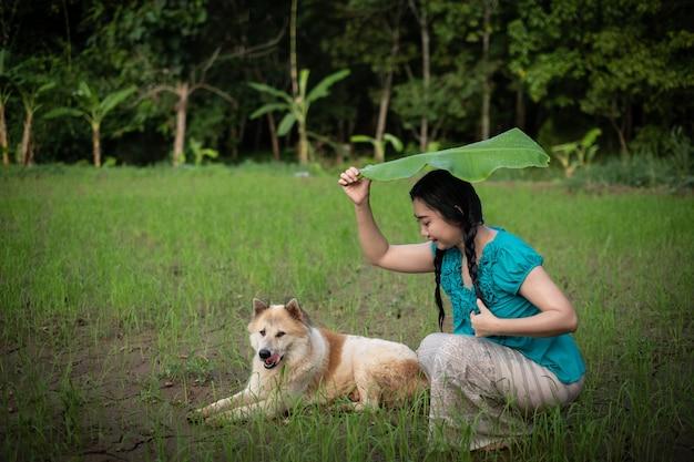 緑の庭の背景にバナナの葉を保持している黒髪の若いアジアの女性の肖像画