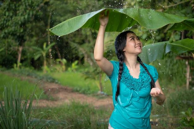 Портрет молодой азиатской женщины с черными волосами, держащей банановый лист под дождем