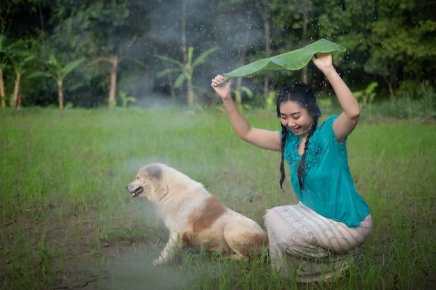 雨の中でバナナの葉を保持している黒髪の若いアジアの女性の肖像画