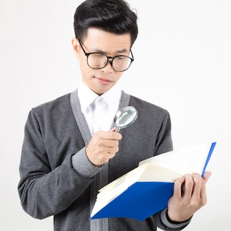 책을 읽고 돋보기를 들고 젊은 아시아 학생의 초상화. 흰색 배경에 촬영 스튜디오입니다. 교육을위한 개념