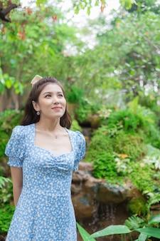 정원 배경에서 행복하게 웃고 있는 파란 드레스를 입은 젊은 아시아 여성의 초상화