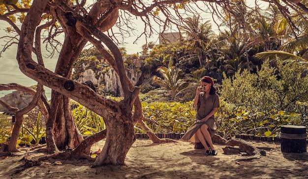 メキシコのトゥルムで雄大な木の下に座っている若いアジアの女の子の肖像画。