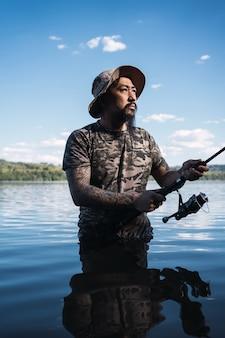 釣りをしている若いアジア人男性の肖像画-tシャツとカモフラージュされた帽子を持つアジアのひげを生やした男性。