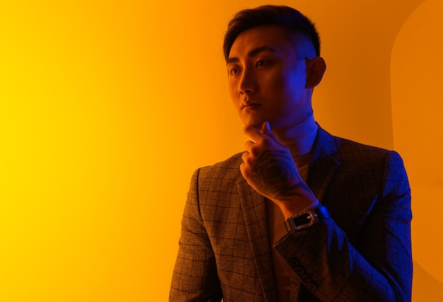Портрет молодого азиатского человека, стоящего над желтым