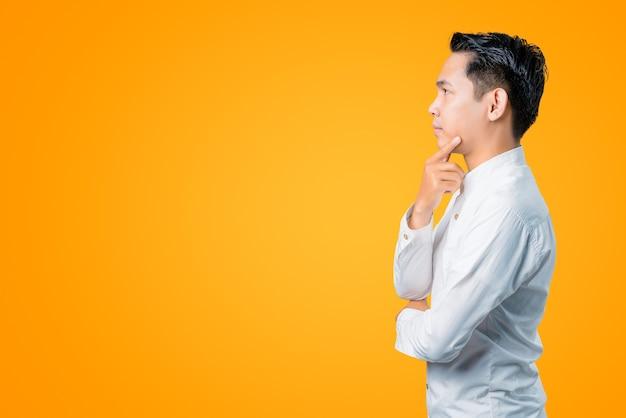 考えて横を向いている若いアジア人男性のポートレート