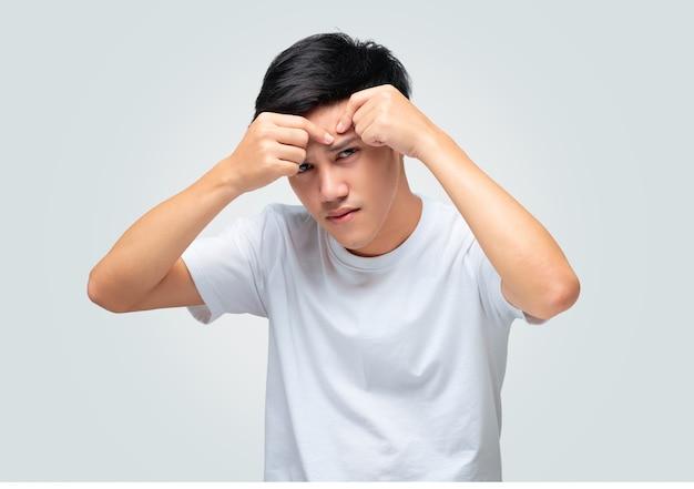 그의 손을 사용하는 젊은 아시아 남자의 초상화는 이마에 여드름을 압착