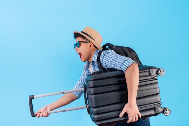 荷物を持って、興奮して、興奮している若いアジア人の肖像画。分離された青に