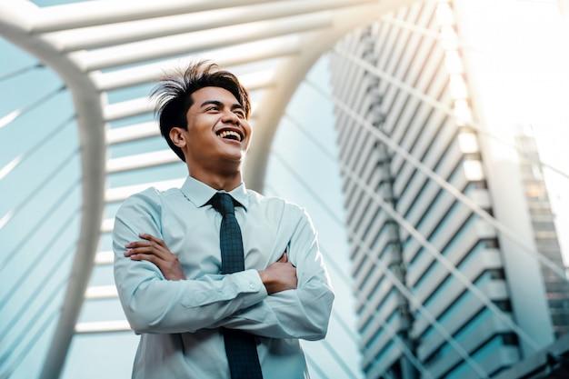 都市の若いアジアの笑みを浮かべてビジネスマンの肖像画。組んだ腕とよそ見