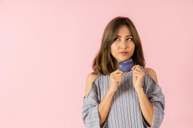 Портрет молодой азиатской женщины, держащей кредитную карту. она думает о покупках. изолированные на розовом фоне