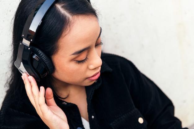 콘크리트 벽에 기대어 야외에서 음악을 들으며 헤드폰을 끼고 있는 젊은 아시아 여성의 초상화