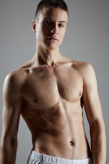 회색 배경에 펌핑 업 몸통을 가진 젊은 선수의 초상화 자른보기. 고품질 사진