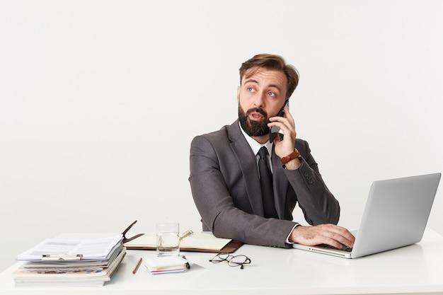 電話で重要なビジネス上の問題について話し合っている若い魅力的なひげを生やしたビジネスマンの肖像画。オフィスのデスクトップに座って、ラップトップで働いて、ネクタイをしたスーツを着ています。