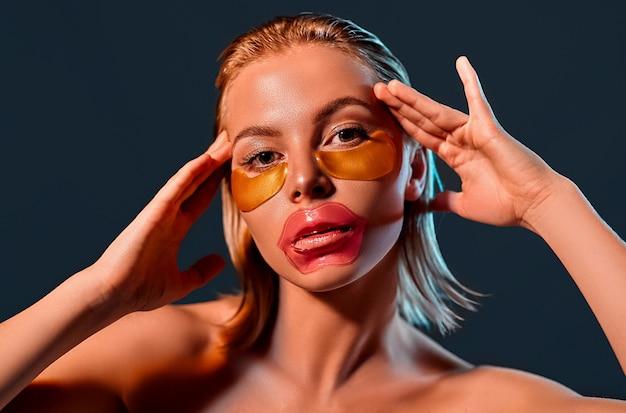 Портрет молодой привлекательной блондинки с блестящей кожей с пятнами на губах и под глазами на черной стене