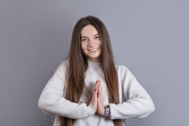 灰色のスタジオの背景に何かを求めて手のひらを一緒に折りたたむ暗い長い髪の若い魅力的な女の子の肖像画。テキストの場所。