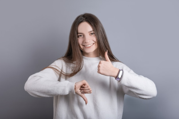 暗い長い髪の若い魅力的な女の子の肖像画は、灰色のスタジオの背景に良いか悪いか、親指を上下に示しています。テキストの場所。