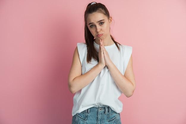 핑크 스튜디오 배경에 뭔가를 요구하는 손바닥이 함께 접혀있는 젊은 매력적인 여자의 초상화