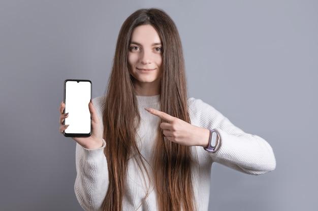 簡単に笑顔で指を指す暗い長い髪の若い魅力的な女の子の女性の肖像画