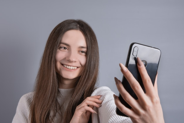 暗い長い髪の若い魅力的な女の子の女性の肖像画は、灰色のスタジオの背景にビデオ通話で話している電話で自分撮りを取ります。テキストの場所。コピースペースあり