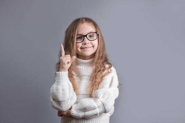 회색 스튜디오 배경에 표시 하 고 손가락을 가리키는 웃 고 흰색 스웨터에 금발 머리를 가진 젊은 매력적인 어린 소녀의 초상화. 텍스트를 놓습니다.