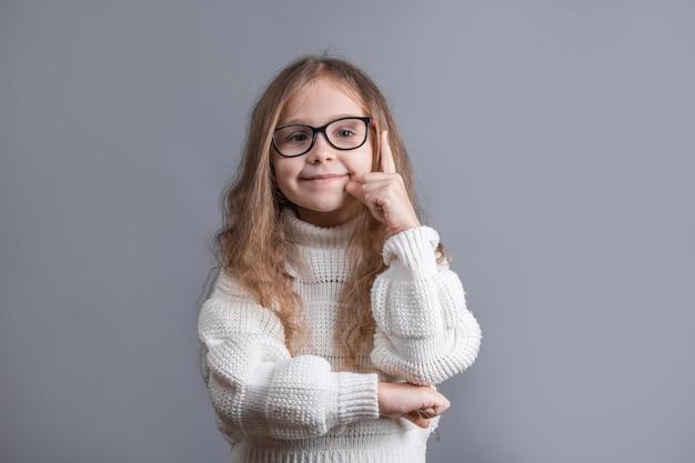 白いセーターに金髪の若い魅力的な少女の肖像画を見せて、指を上に向けて笑って、アイデア
