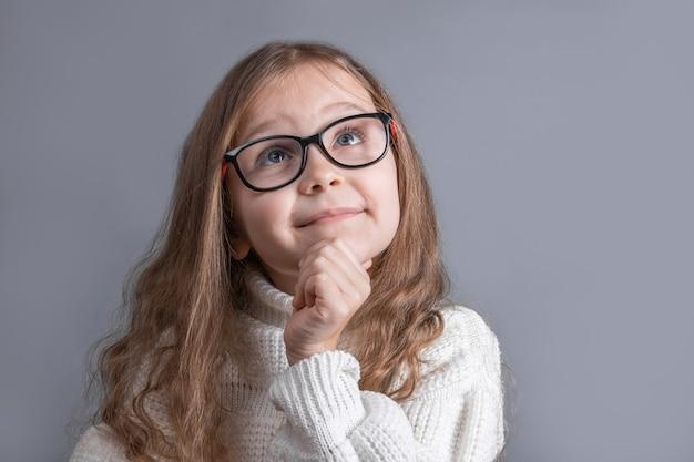 思慮深く目をそらし、灰色のスタジオの背景に考え、計画している白いセーターのブロンドの髪を持つ若い魅力的な少女の肖像画。テキストの場所。