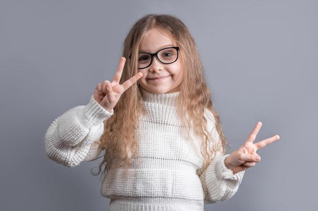 灰色のスタジオの背景にvサイン、ピースサイン、両手で勝利のジェスチャーを示すセーターのブロンドの髪を持つ若い魅力的な少女の肖像画。