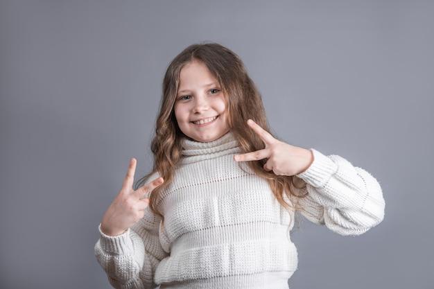 Vサイン、ピースサイン、灰色のスタジオの背景に両手で勝利のジェスチャーを示すセーターのブロンドの髪を持つ若い魅力的な少女の肖像画。
