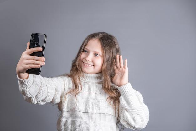Портрет молодой привлекательной маленькой девочки со светлыми длинными распущенными волосами в белом свитере с мобильным телефоном делает селфи-переговоры по видеосвязи