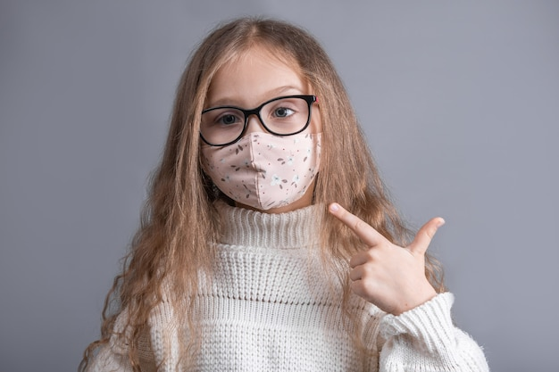Портрет молодой привлекательной маленькой девочки со светлыми длинными распущенными волосами в белом свитере указывает пальцем на защитную маску на ее лице на сером студийном фоне.