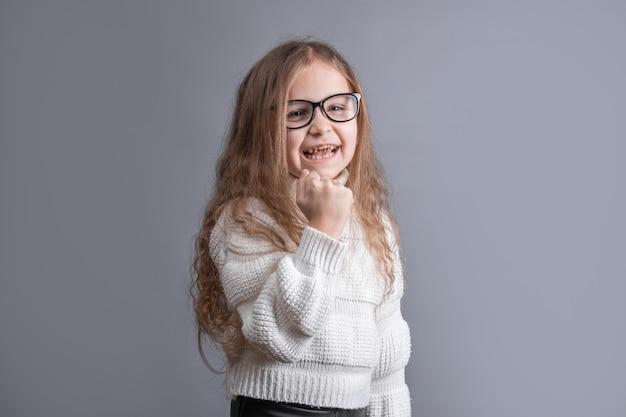 흰색 스웨터에 금발 긴 흐르는 머리를 가진 젊은 매력적인 어린 소녀의 초상화는 회색 스튜디오 배경에 성공을 축하하는 주먹 인상. 공간을 복사하십시오.
