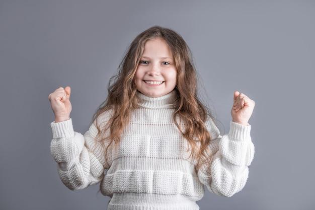 Портрет молодой привлекательной маленькой девочки со светлыми длинными распущенными волосами в белом свитере радуется ее победе, подняв руки вверх на сером студийном фоне. место для текста. скопируйте пространство.