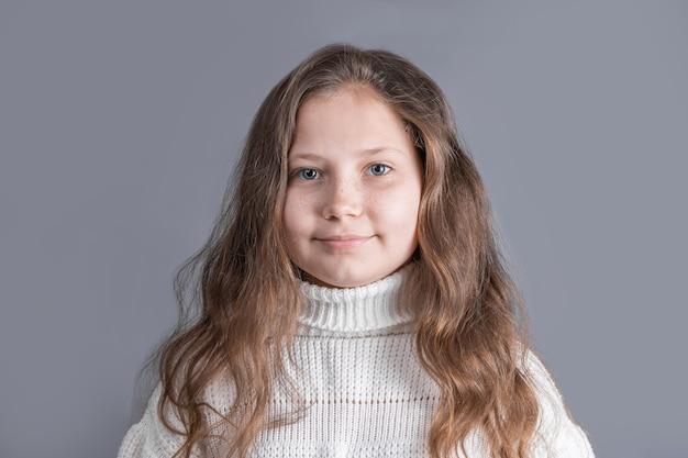회색 스튜디오 배경에 웃 고 흰색 스웨터에 금발 긴 흐르는 머리를 가진 젊은 매력적인 어린 소녀의 초상화. 텍스트를 놓습니다. 공간을 복사하십시오.