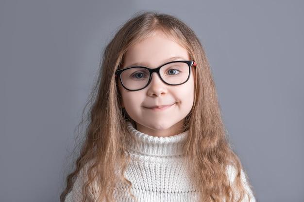 회색 스튜디오 배경에 웃 고 흰색 스웨터에 금발 긴 흐르는 머리를 가진 젊은 매력적인 어린 소녀의 초상화. 텍스트를 놓습니다. 공간을 복사하십시오. 프리미엄 사진
