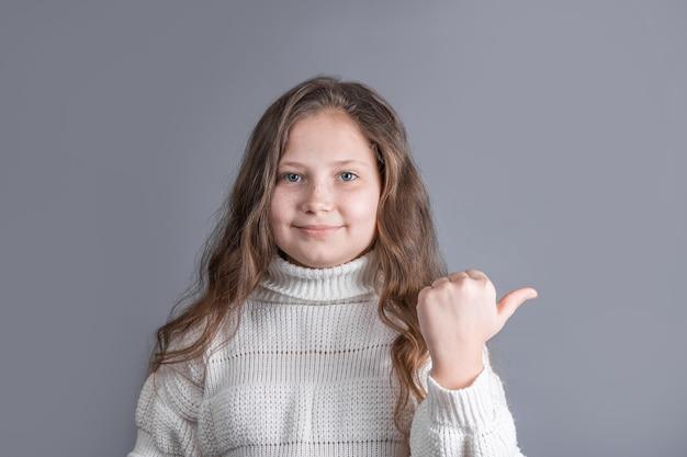 Портрет молодой привлекательной маленькой девочки со светлыми длинными распущенными волосами в белом улыбающемся свитере показывает палец руки в сторону на сером фоне студии. место для текста.