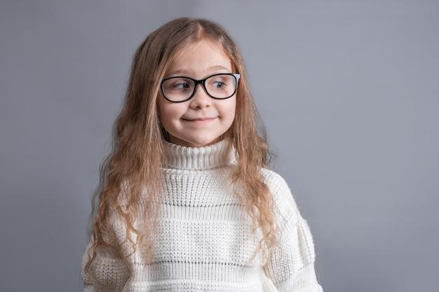 Портрет молодой привлекательной маленькой девочки со светлыми длинными распущенными волосами в белом свитере, задумчиво глядя в сторону на сером фоне студии. скопируйте пространство.