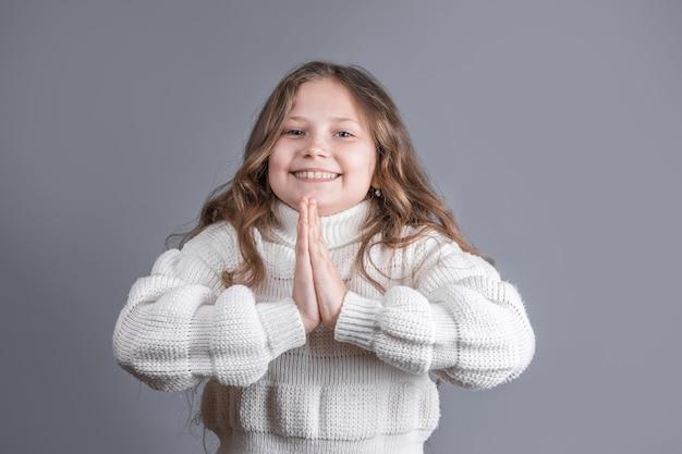 미소를 요구하는 흰색 스웨터에 금발 긴 흐르는 머리를 가진 젊은 매력적인 어린 소녀의 초상화, 회색 스튜디오 배경에기도. 공간을 복사하십시오.