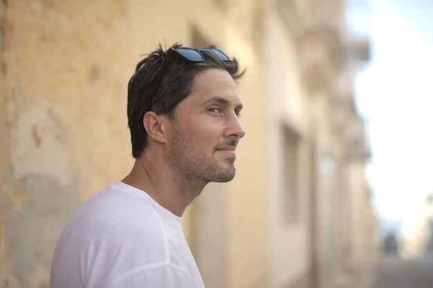 Портрет молодого привлекательного мужчины в солнечных очках, позирующего у стены в солнечный день