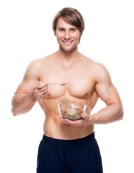 フレークを食べる若い魅力的な筋肉の男の肖像画-白い壁に隔離。